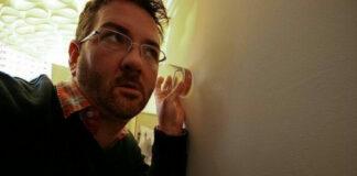 egy férfi egy pohárral halgatja a falat