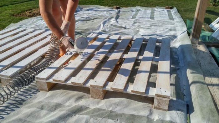 person painting wooden pallets
