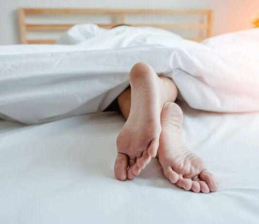 The legs of a person sleeping on a bed