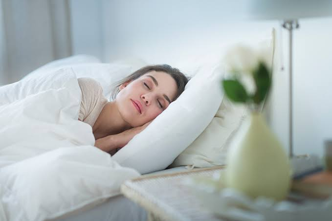 lady sleeping on a bed beside a flower vase