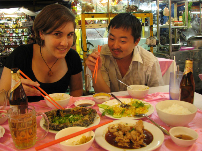 man and woman eating local food