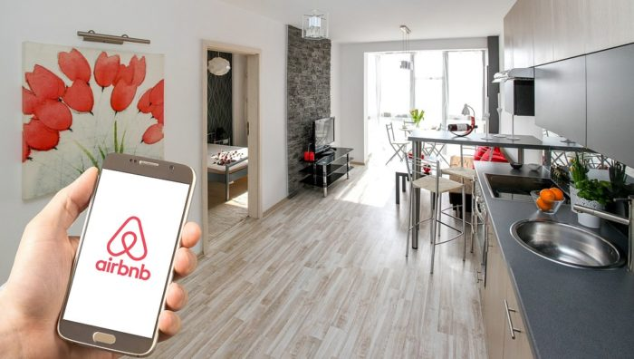 a man in a house, holding a phone showing the airbnb logo