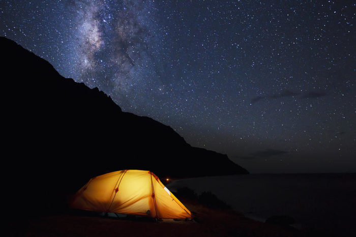 A person camping under an open sky