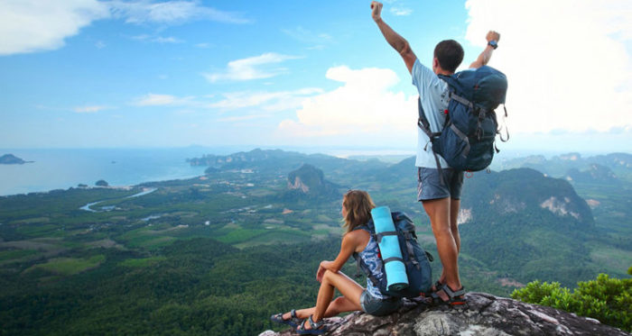 man and woman on a rock enjoying the view of nature