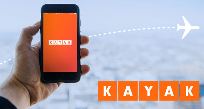 the kayak app launching on a phone held by a man over a demonstrative background