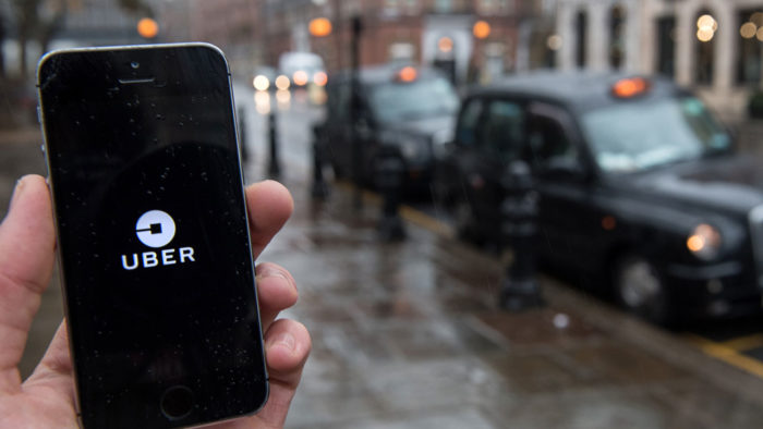 a person holds a phone showing the uber logo under mild rain in a street of cars