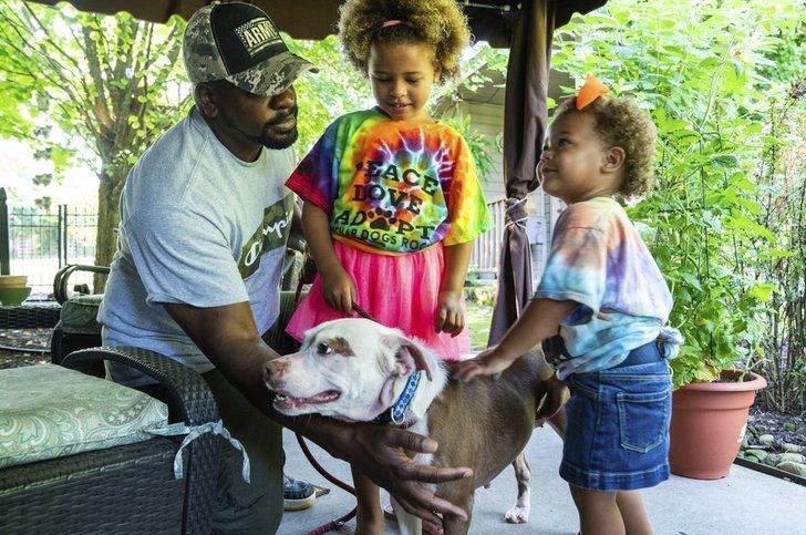 Man med två barn tar hand om ett djur