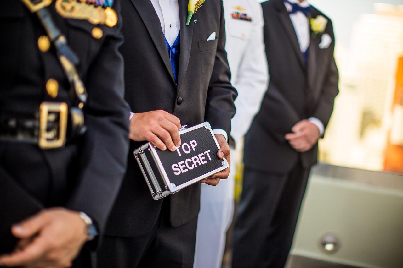 folk på rad varav en håller en väska som det står Top Secret på