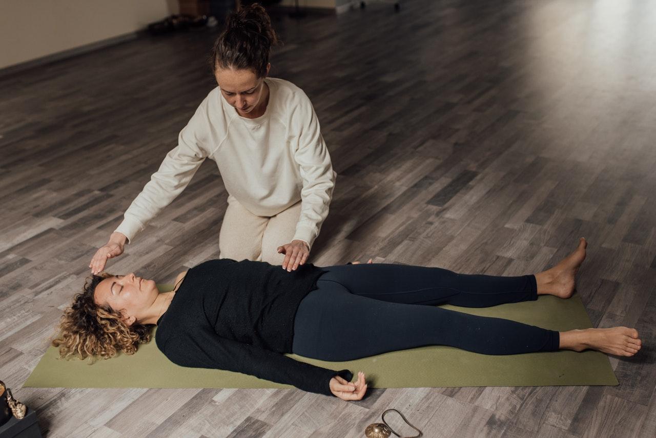 kvinna ligger ner på golvet och andas medan annan kvinna står ovanför och guidar