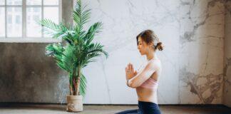 Kvinna utför meditation sittandes med händer ihop framför sig