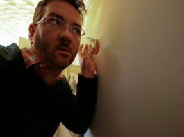 man uses a glass cup to listen in on a wall
